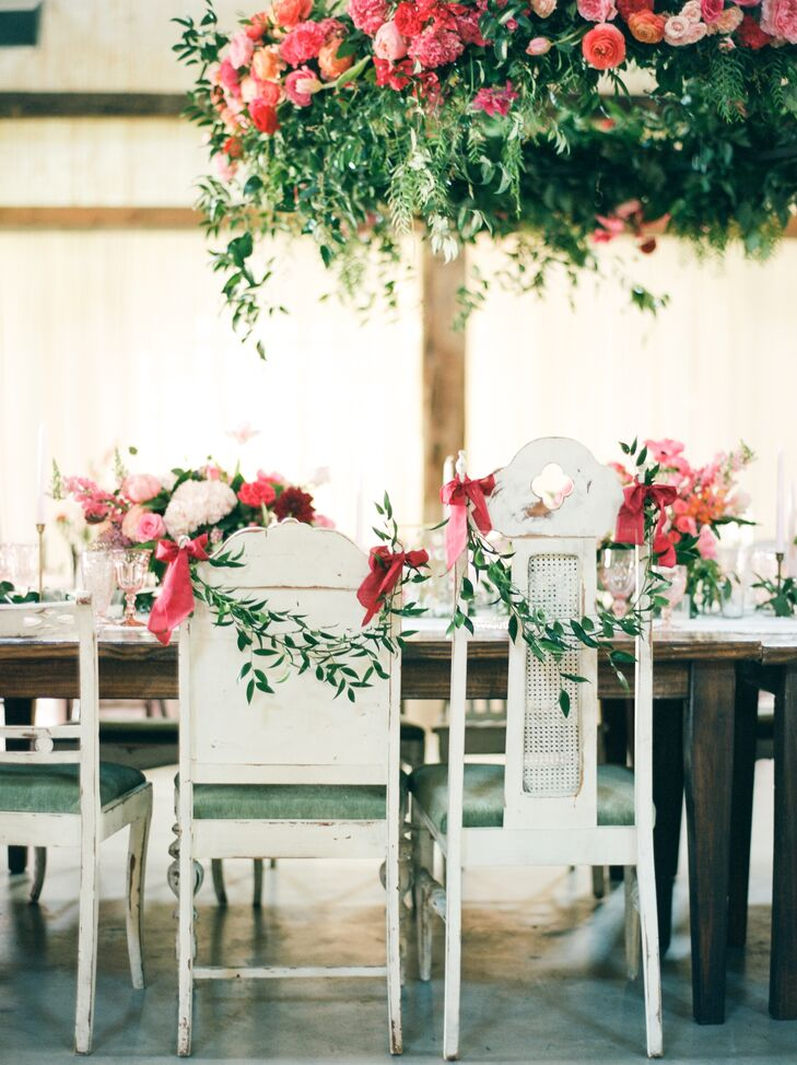 Delicate green garlands were looped over Deborah and Elton's chairs at the barn reception at Chandelier Grove in Tomball, Texas.