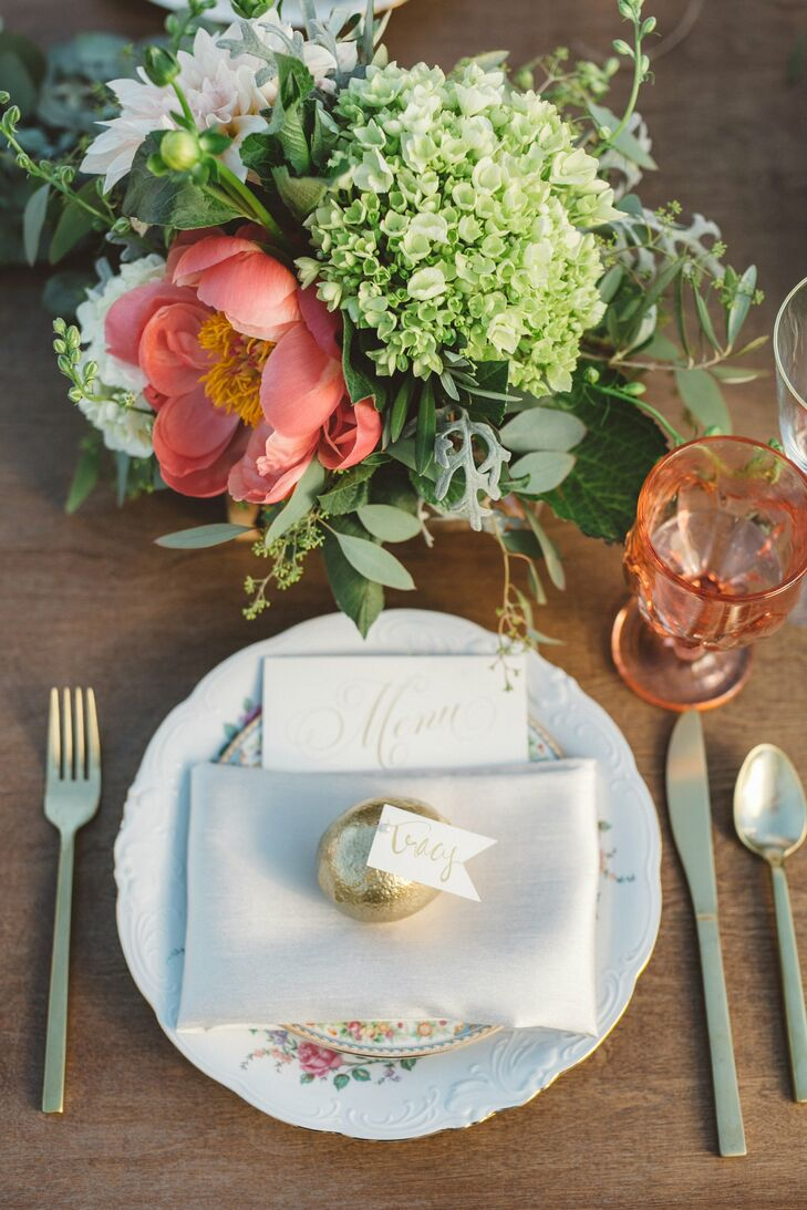 """Long wooden feasting tables were set with vintage china in various rose patterns and soft-colored glassware. """"I loved that the place setting is something I could have seen in my family's heirloom chest and that it resembled my favorite things about other weddings I've designed,"""" says Tracy, who works as an event planner. """"Each place setting was marked with a miniature paper flag attached to a golden citrus. The shimmer caught the light just right and glowed as the sun began to set."""""""