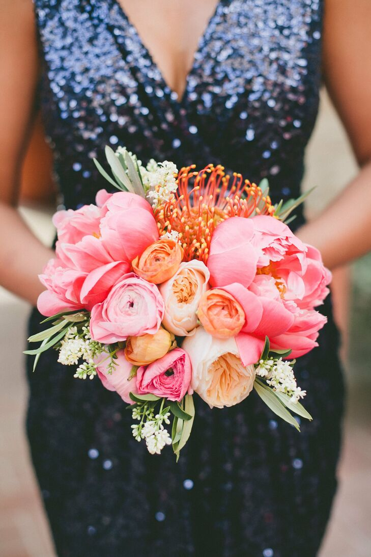 Fully bloomed peonies and protea added and depth and texture to the bridesmaids' cheerful pink, orange and peach bouquets.