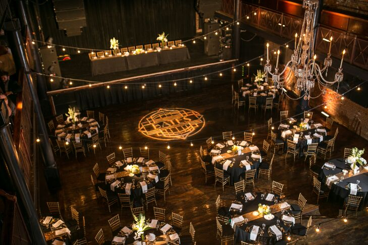"""The reception took place inside NorVa in Norfolk, Virginia, where dining tables filled the dimly lit space. """"All of our dining tables were round, while the wedding party sat at a long banquet table on the stage,"""" Lindsey says. """"It allowed us to be with our guests while having dinner, but removed enough that we could eat and enjoy our meal."""""""