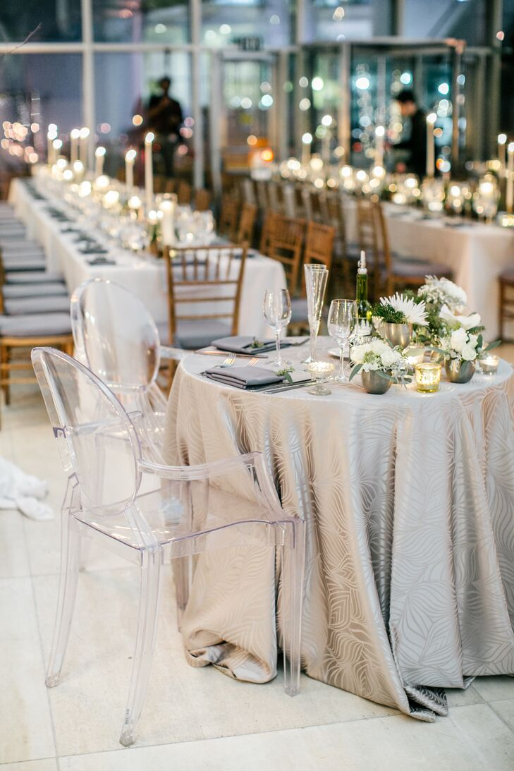 The sweetheart table was covered in a patterned silver tablecloth and decorated with small silver vases of white flowers, including chrysanthemums and roses. The chairs at the sweetheart table were modern and transparent.