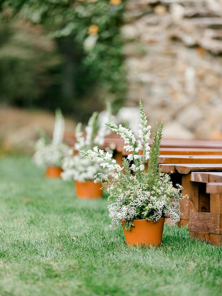 Potted wildflower plants along wedding ceremony aisle at outdoor wedding
