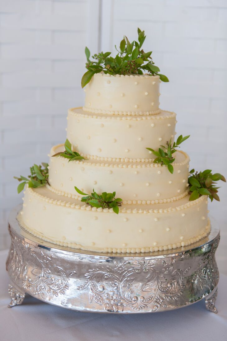 The wedding cake was iced in off-white and featured small bunches of fresh greenery. Additional decorative dots of icing added texture. The cake's flavor? Sarah's favorite: Funfetti.