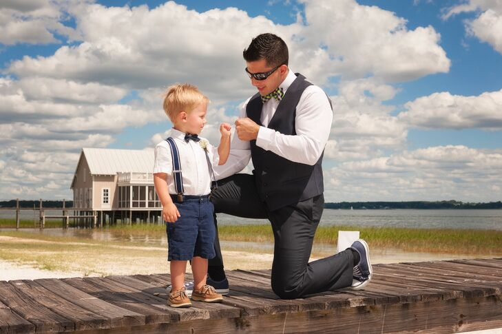 The ring bearer's outfit brought out Holly and Jaime's navy wedding color with a sweet touch. He was dressed for the waterfront wedding in neutral Sperry boat shoes, a white shirt, navy suspenders and matching pants as a navy bow tie finished the look.