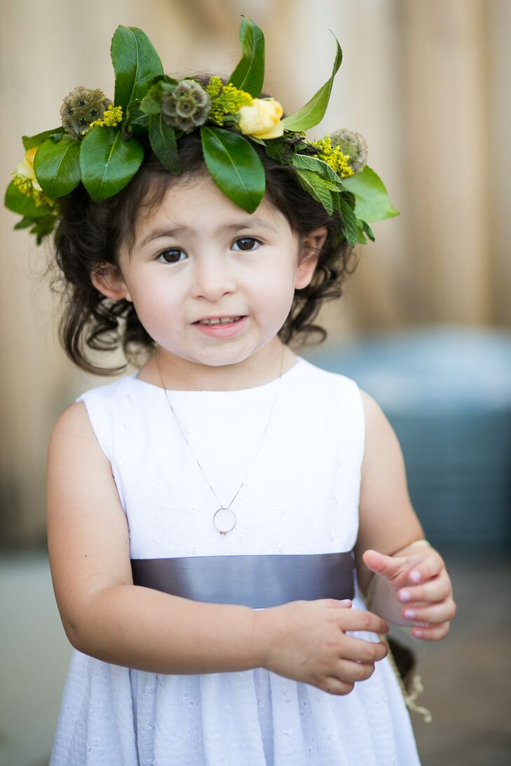 Their adorable flower girl wore a boho-chic flower crown made up of leafy greens, yellow roses and scabiosa pods. The hair accessory added a nice natural touch to her white and gray ensemble.