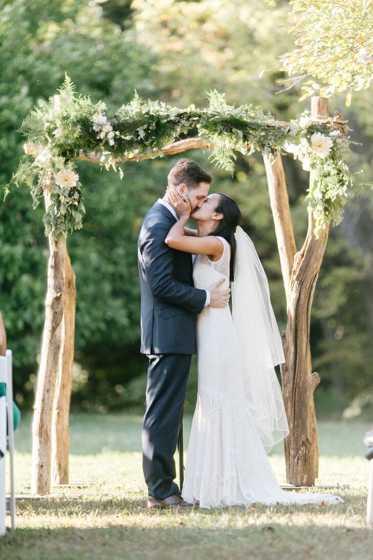 Newlyweds' First Kiss Under Birch Wedding Arch