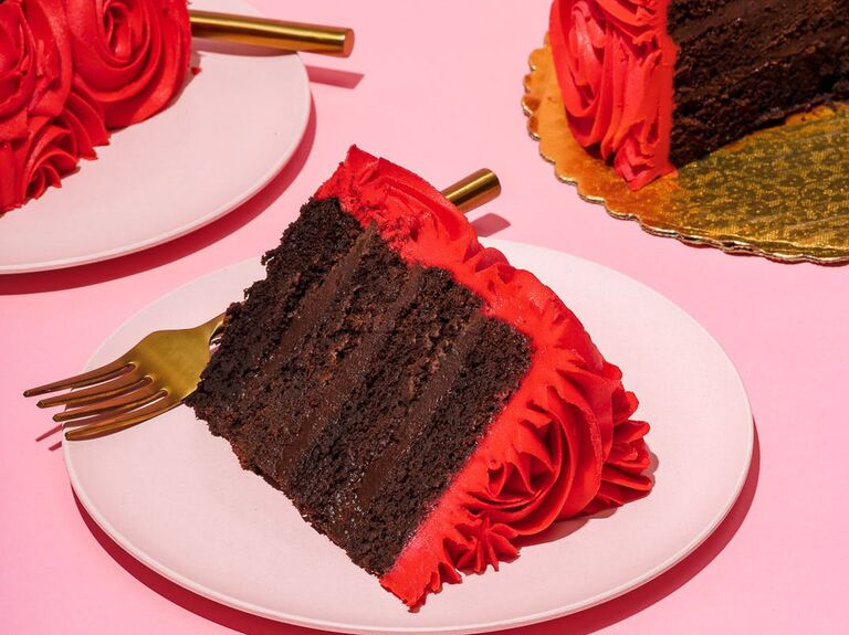 Decadent layered chocolate cake with red frosting cut into slices