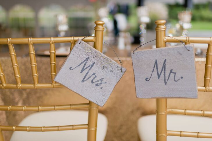 """""""Mr."""" and """"Mrs."""" signs hung over the back of Katie's and Joe's gold chiavari chairs at the reception."""