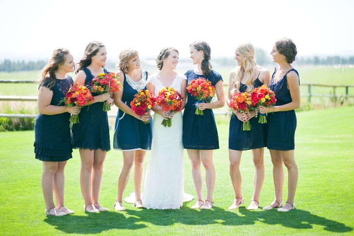 """Sara stood with her bridesmaids outside on the property, all dressed in navy blue short dresses with different styles and lace accents. """"I let my bridesmaids find their own dresses so they would be able to find something they felt most flattering in, and to also to give some variety in styles,"""" Sara says."""