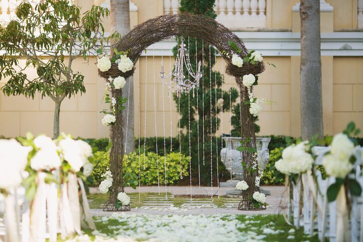 Amina and Brian were wed in The Ritz-Carlton, Sarasota garden under a vine-wrapped wedding arch accented with crystals,  white hydrangeas and a crystal chandelier.