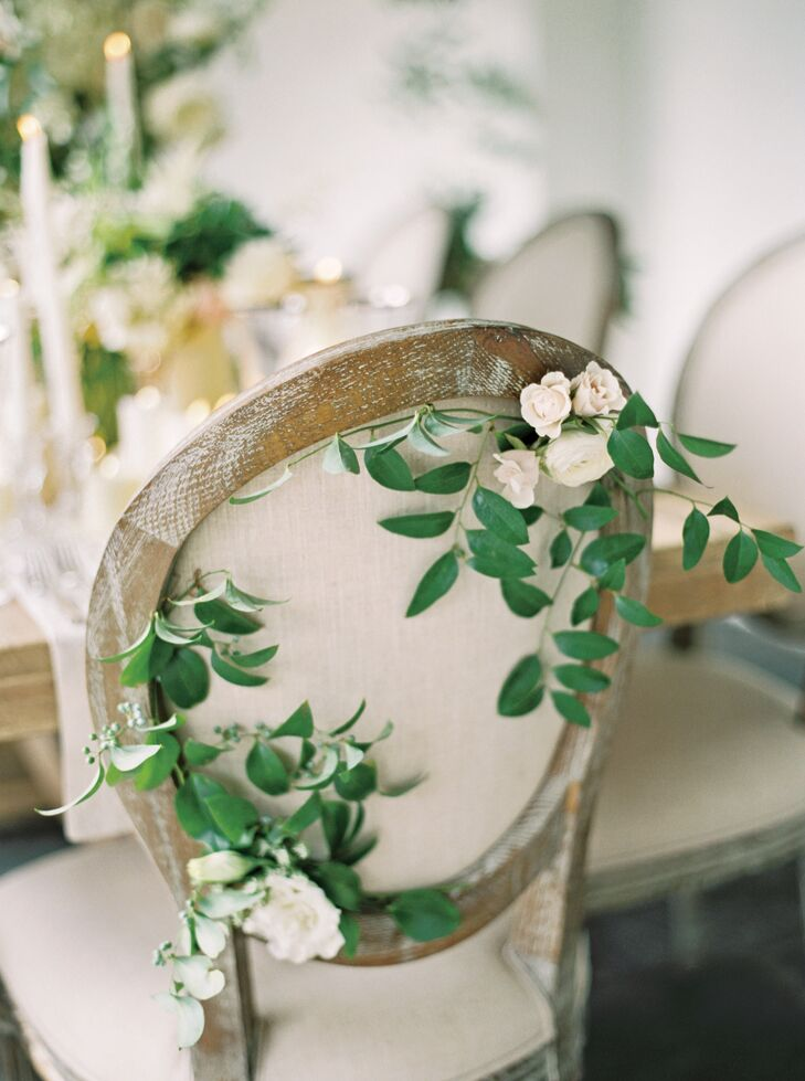 Wedding reception chairs with greenery accents