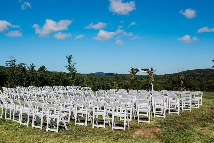 Natural Ceremony Site with Wood Arch and White Folding Chairs