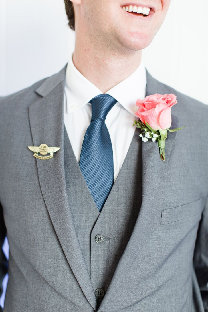 The groomsmen wore matching gray three-piece suits with navy ties and coral rose boutonnieres. The pilot wings pin wedding favors added a nod to the airplane theme.