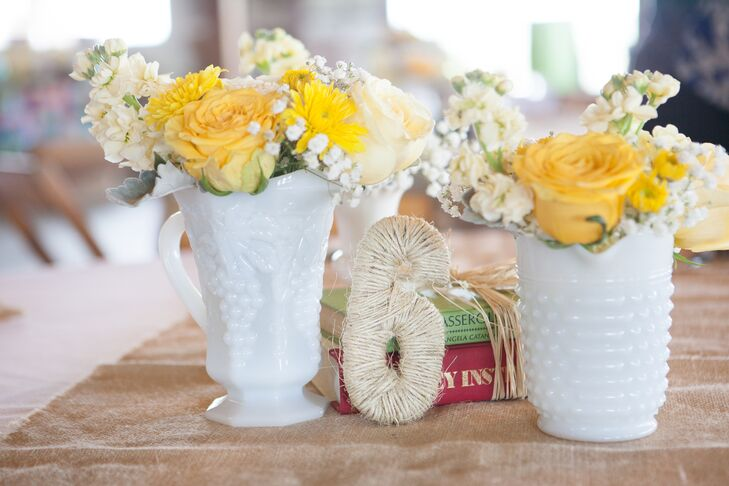Drawing on the summer season for inspiration, Jennifer and Whitney chose a cheerful color palette of yellow and ivory with pops of blue. The couple, along with the help of their close family and friends, made all of the centerpieces themselves. They filled milk glasses vases with seasonal blooms like roses, stock and chrystanthemums and arranged them with burlap accents and vintage books to give the tables a rustic touch.