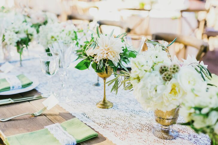 The event's earthy theme took root again at the reception, where tables were set with silver flower vases filled with garden roses, peonies, scabiosa pods, balsa wood flowers, green hydrangeas and verdant eucalyptus. Fragrant bay leaf garlands were laid alongside lace runners down the center of the longer farm tables.