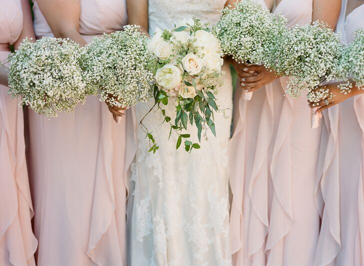 The bridesmaids wore blush dresses and held baby's breath bouquets, while Kelsie carried a neutral arrangement of hydrangeas, roses, peonies and greenery.