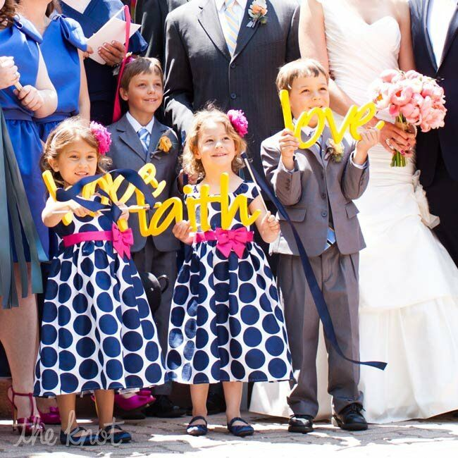 For something unexpected, the couple's flower girls and ring bearers carried bright-yellow custom signs down the ceremony aisle.