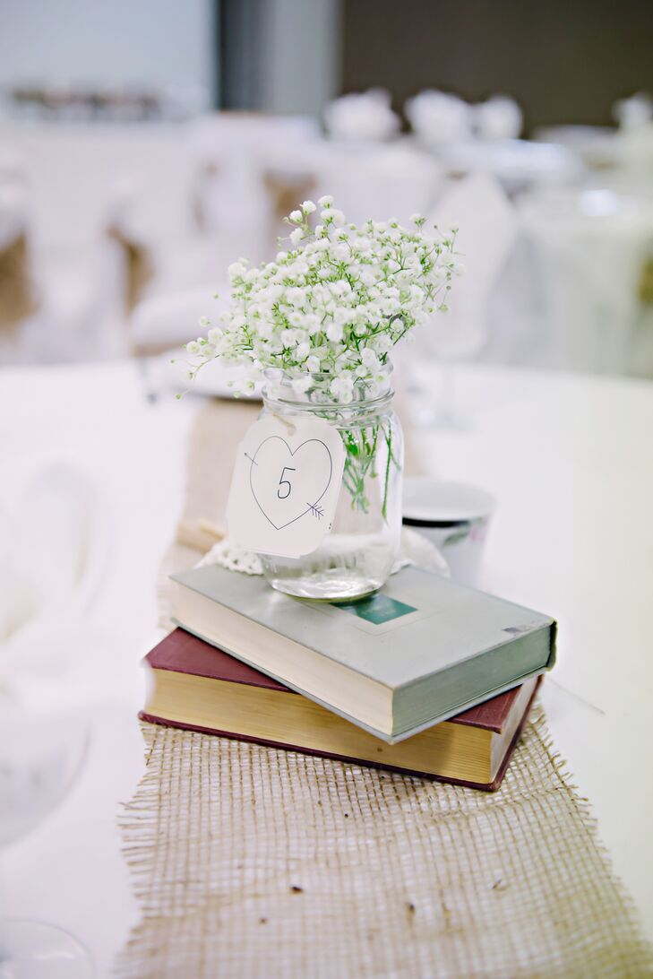 Stacks of hardcover books were placed at the center of each table, serving as the base for delicate arrangements of baby's breath mason jar centerpieces.
