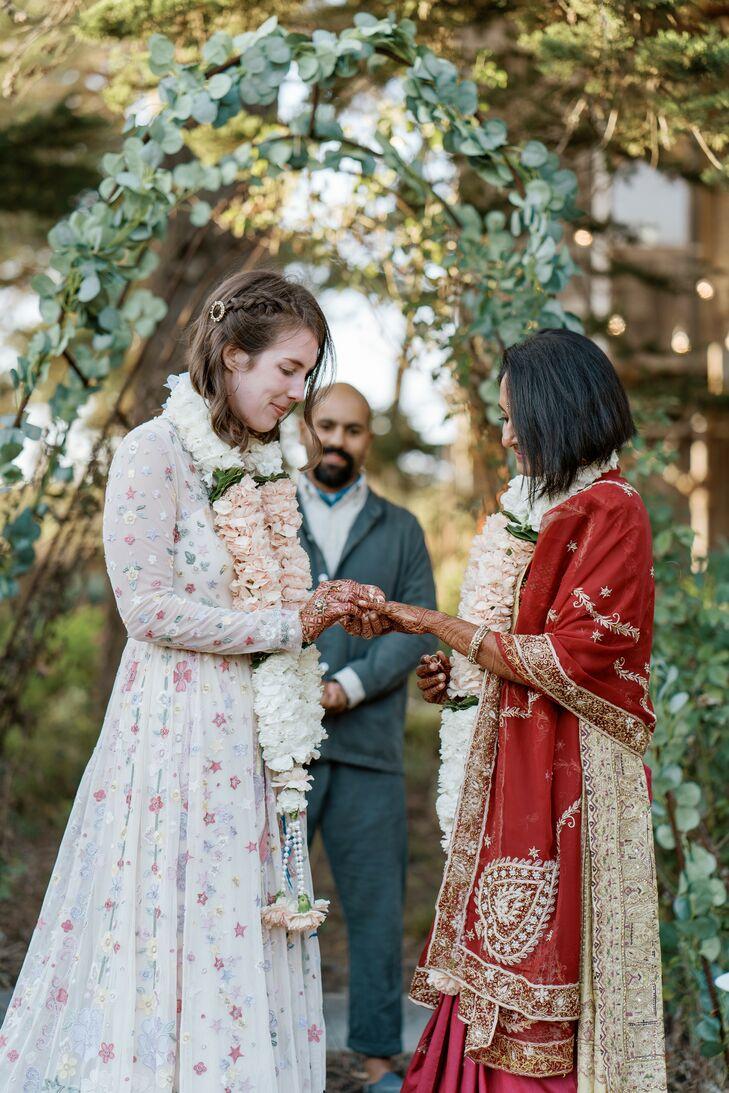 Couple Exchanging Wedding Rings While Wearing Marigold Garlands