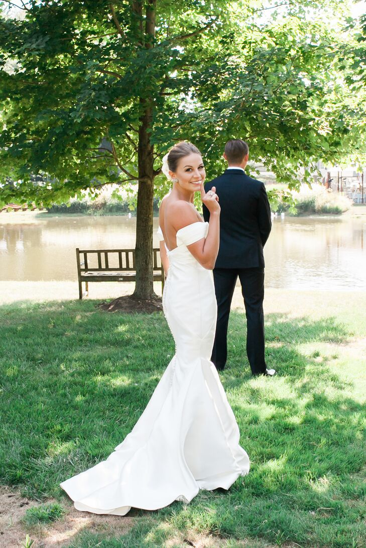 """Drawing inspiration from the wedding's fusion of laid-back and elegant styles, Rebecca opted for a simple, chic Kelly Faetanini gown. The silk chiffon dress featured a mermaid-style silhouette with a low-cut back and off-the-shoulder neckline, as well as fabric-covered buttons running down the back. """"Words can hardly describe the feeling as I walked down the aisle toward the man of my dreams with my dad by my side, veil blowing in the breeze and the sun shinning through the trees behind us, all in my backyard. It was simply magical,"""" Rebecca says."""