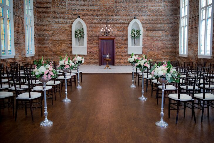 """""""We were married at Saint Thomas Preservation Hall in downtown Wilmington, North Carolina,"""" Elizabeth says. """"It is a restored former Catholic Church built in 1847 as the first African American Catholic Church in the state of North Carolina. It is a landmark in Wilmington's Historic District and is listed on the National Historic Register. The warm exposed brick walls with sky high ceilings and stained glass windows all reflected a sense of history and beauty. It was a quiet, private gem in the middle of downtown."""""""