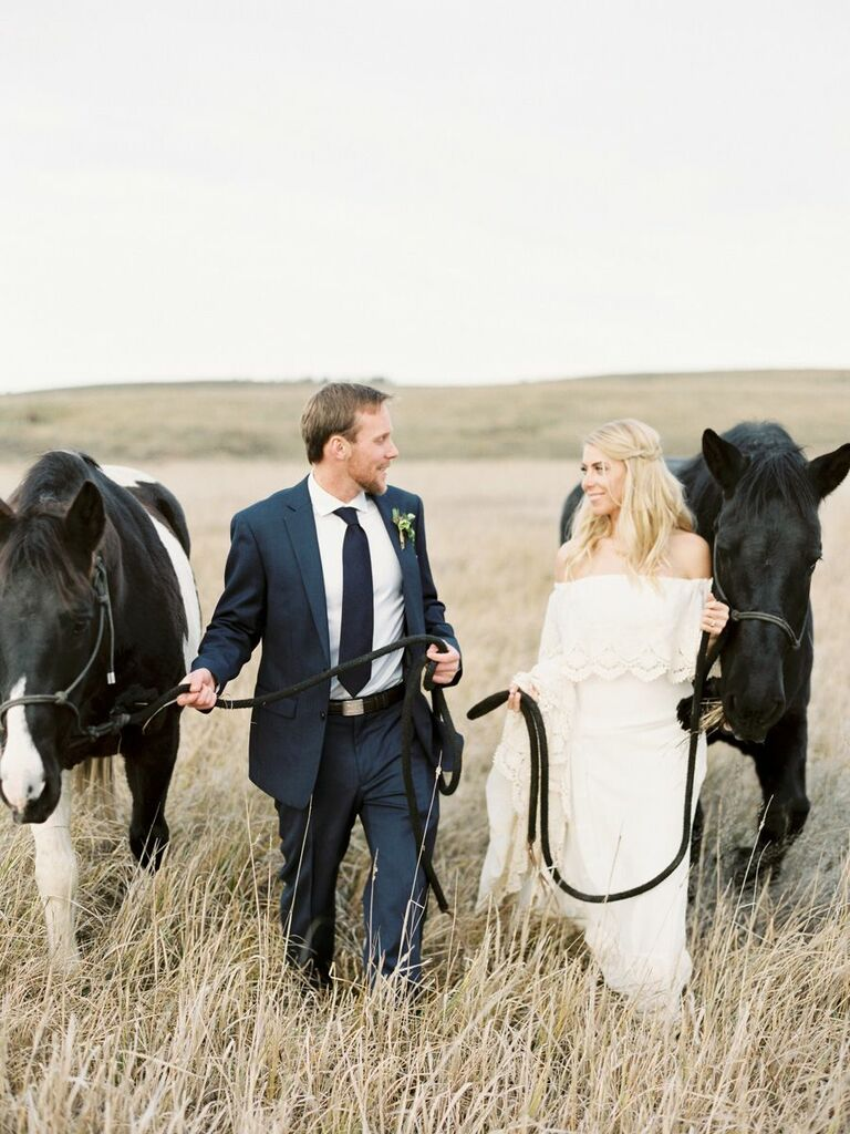 bride and groom walking with horses
