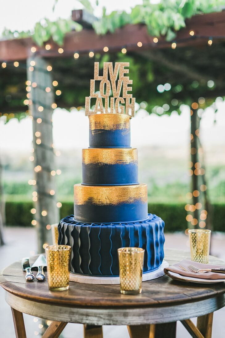 """In a nod to the couple's theme, a gold """"live, love, laugh"""" topper and gilded brush strokes adorned the navy wedding cake."""