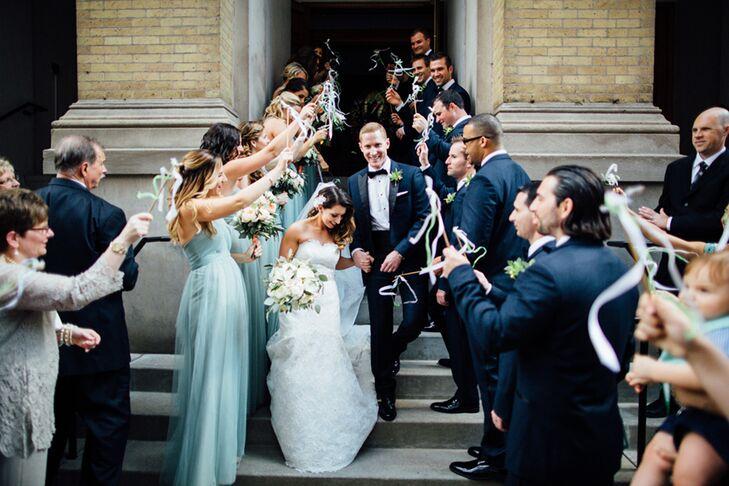Lauren's aunt and uncle made 100 ribbon wands waved by guests as the couple left Assumption Catholic Church in Chicago, Illinois.