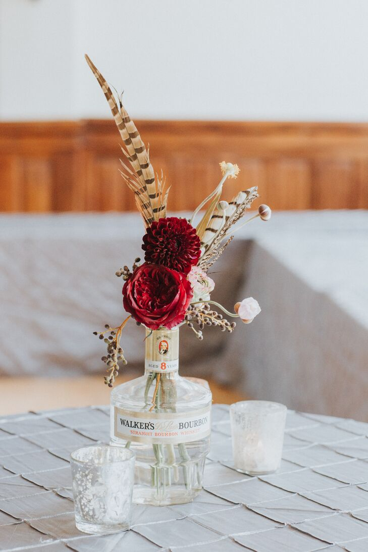 Bourbon bottles were repurposed as vases and filled with feathers and fall blooms.