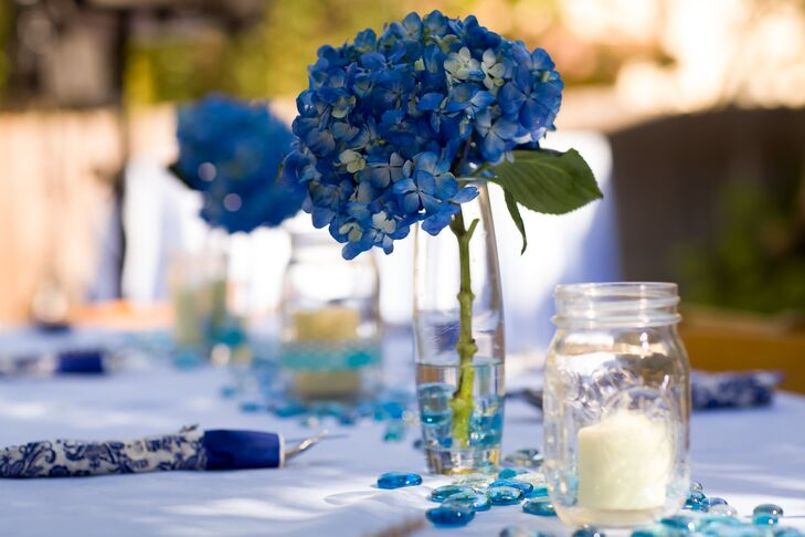 At the reception, dining tables were decorated with small blue stones scattered across the linens. Blue hydrangeas purchased from a local market were placed in simple glass vases, which alternated as table centerpieces with candles in glass mason jars.