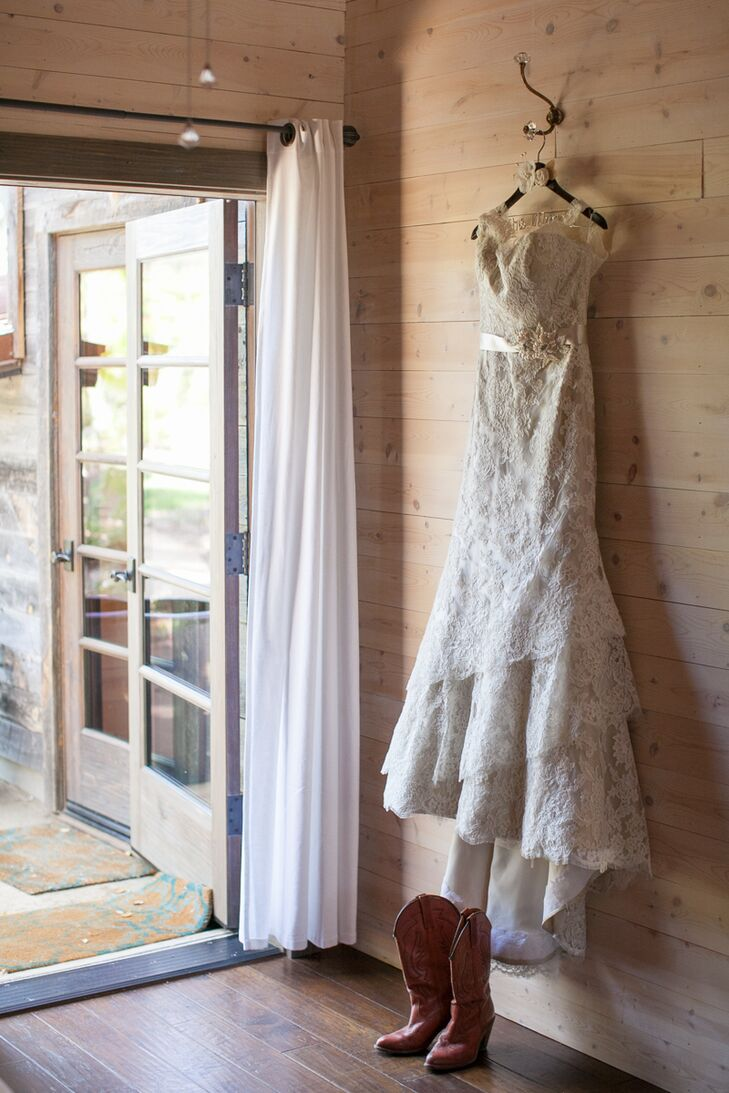 Nicole's champagne-colored wedding dress was made of silk and accented with eyelash lace, while her bridesmaids wore emerald green dresses that they picked out themselves. They all wore a pair of vintage cowboy boots in different hues of brown to fit with the wedding's rustic style.