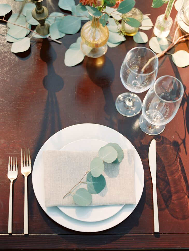 At the reception, long wooden tables accommodated dozens of guests. Each simple setting included cream plates, a textured beige napkin, gold flatware and delicate eucalyptus twigs.