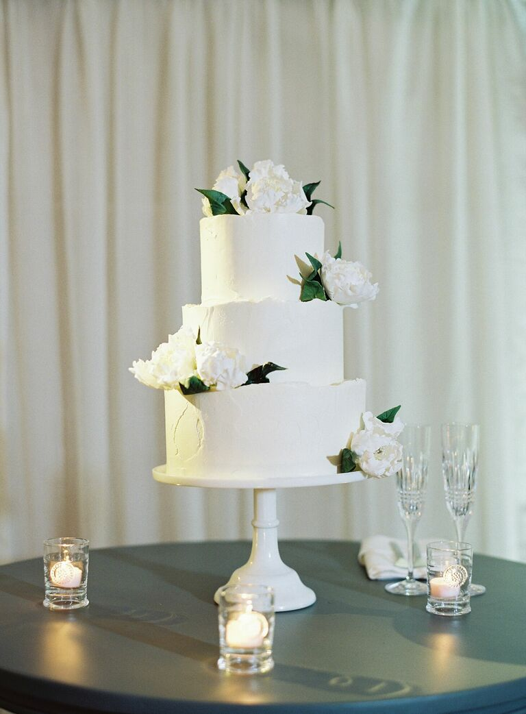 White three-tier wedding cake with white cake stand