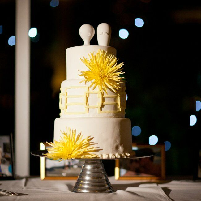 The white three-tiered wedding cake featured Jonathan Adler salt-and-pepper shakers on top.