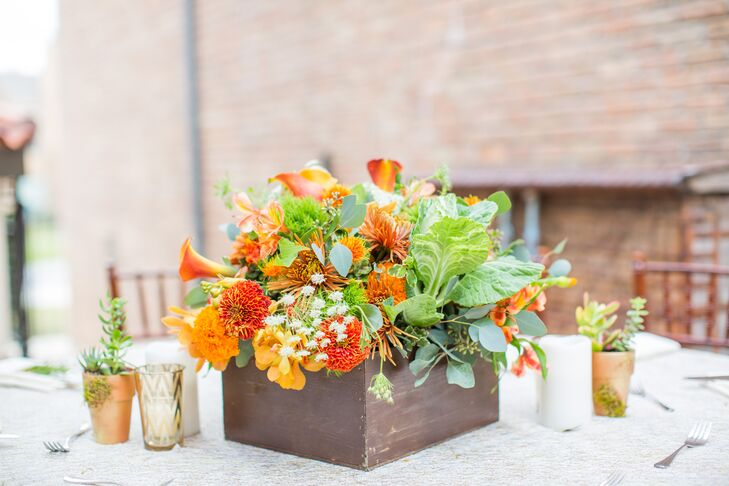 At the reception, round dining tables with khaki or burlap linens and textured champagne overlays were surrounded by mahogany chiavari chairs. Centerpieces of natural greenery and orange blooms in dark wooden boxes, surrounded by gold pillar candles and potted succulents, enhanced the organic atmosphere.
