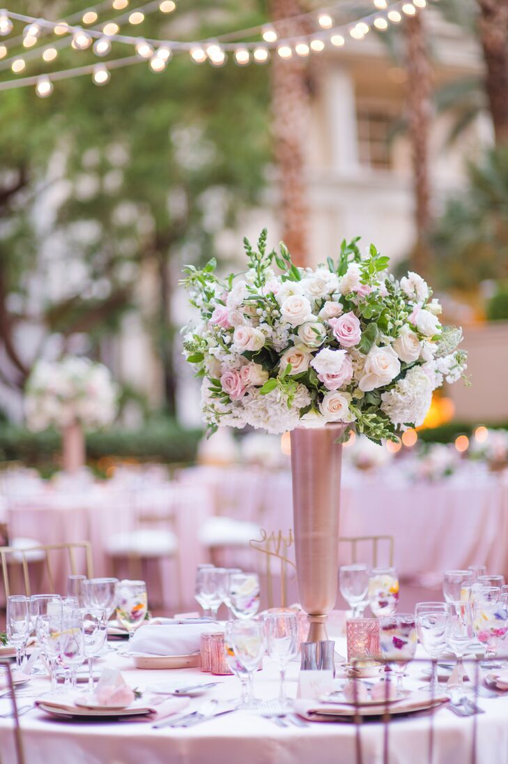 """We wanted a blush and gold style, so the linens were in soft blush color: The centerpieces had flowers that were ivory, white and blush—same as my bridal bouquet,"" Ethel says. ""We also had gold table numbers, gold garden chairs and gold candles."""
