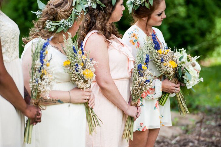 The bridesmaids chose their own dresses for the vineyard wedding. Jules asked them to wear something with a funky vintage feel in a shade of blush, taupe or floral. Her favorite look was her maid of honor (her sister), who wore a floral romper from Entourage Clothing Boutique in Athens, Georgia. The ladies completed their look with baby's breath and eucalyptus leaves and yellow and purple bouquets.