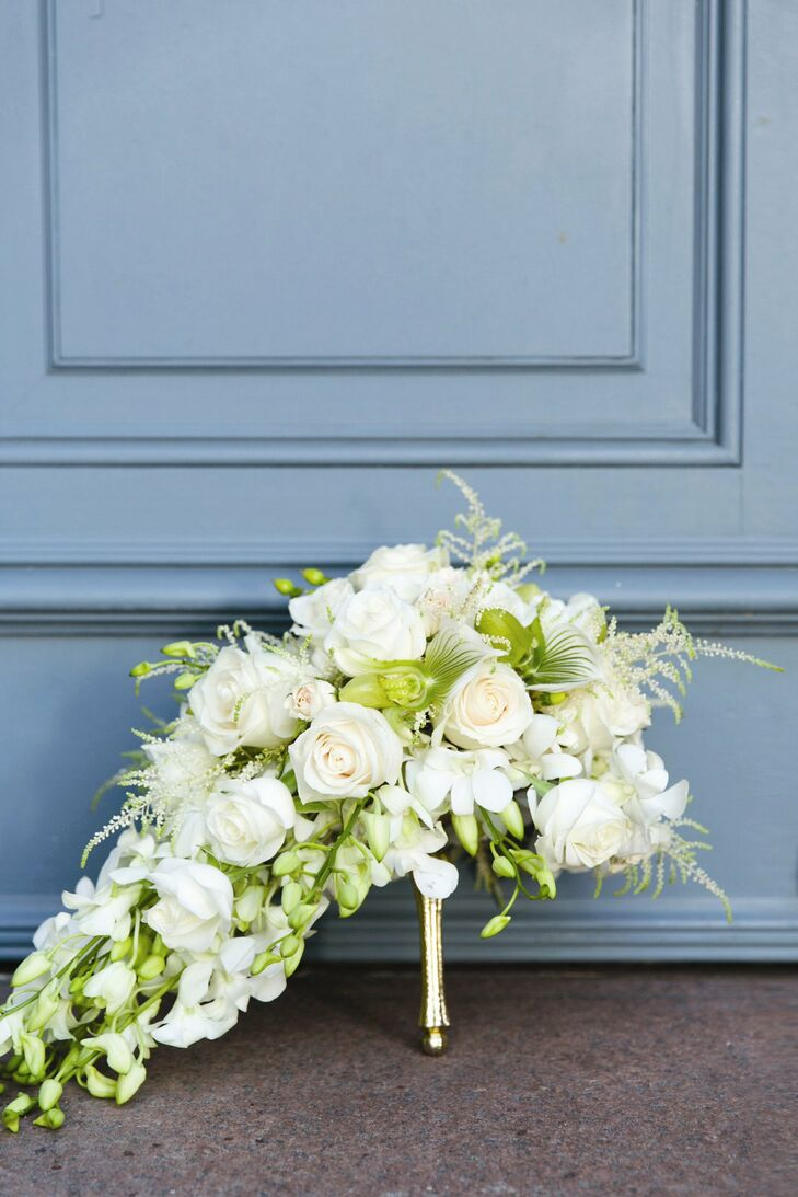 Becca's cascade bridal bouquet had a fresh, garden feel with white cornflower, orchids and roses in shades of ivory, white and green. The bouquet was arranged on a gilded tussy mussy, a Victoria era metal hand-held vase.