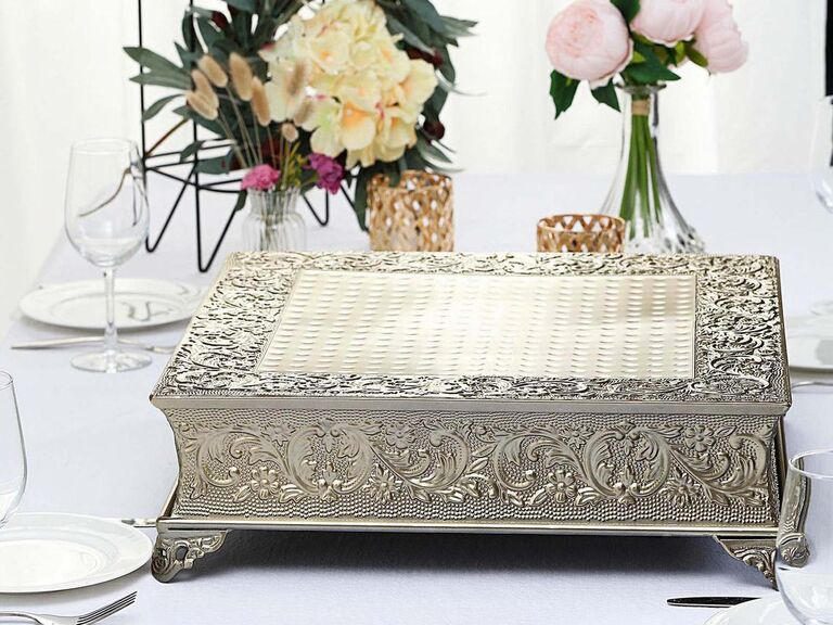 Ornate gold square wedding cake stand with embossing