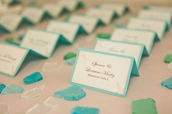 "The couple's 65 guests found their seat listed on a fun place card. Each piece of stationery was backed in the couple's light blue wedding color and accented with a seashell print. Following their ocean and beach theme, the table names included ""the manatee table"" and ""mermaids and sharks."""