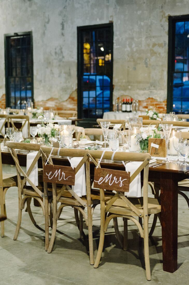"Corinne and John sat at their seats at long wooden farm tables, marked with wooden signs that read ""Mr."" and ""Mrs."" on the backs.They sat surrounded by their wedding party at the reception at Mount Washington Mill Dye House in Baltimore, Maryland."