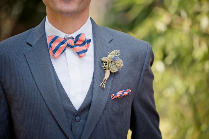 Ryan wore a striped peach and navy blue bow tie with a matching pocket square; his gray suit jacket had a matching vest underneath. He had a succulent, eucalyptus and scabiosa pod boutonniere wrapped together and pinned to his lapel.