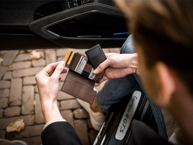Man taking card out of ejected card tray of Ekster wallet