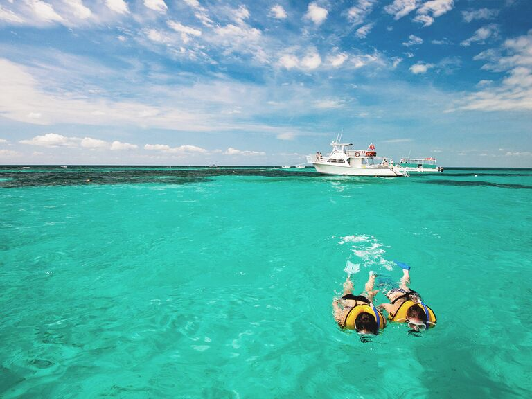 Couple snorkeling through clear water with a boat in the background