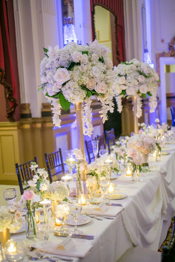 """There's no better way to describe the dining tables other than """"romantic."""" Some had pastel-colored blooms filling out low gold vases, while other tables such as this one had tall gold candelabras holding up overflowing arrangements of hydrangeas and roses. Votive candles surrounded the centerpieces, creating a romantic glow."""