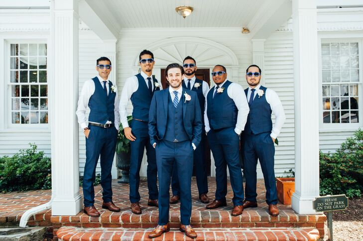 Dennis and his down-the-aisle crew struck the perfect balance of classic elegance and modern cool with navy suits, dark brown oxfords and blue ties. While the groomsmen skipped the suit coat, Dennis distinguished his look from the group with a three-piece suit and a striped tie.