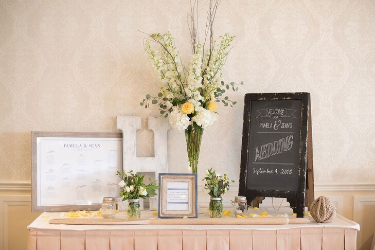 The couple welcomed guests into their reception with a chic entrance table. Surrounded by overflowing arrangements in mason jars and trumpet vases, a navy and white sign from Paper and Lace Collections pointed guests to their seats. Pam and Sean's guest book—a wooden oar—stood out in front of it so guests could leave well wishes before entering the party.