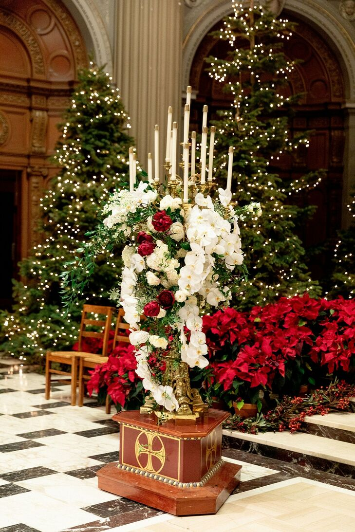 Church Altar with Red and White Flowers and Lit Christmas Trees
