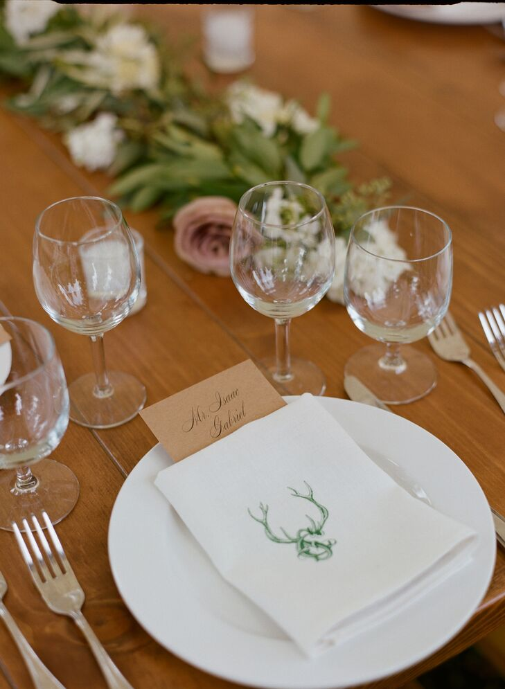 Each place setting had a custom-printed linen napkin with the couple's seal on it. Chutney found a stationery store next to her work in Los Angeles, California, and began drafting their invites right away. She and Steve chose kraft paper with green lettering to match the natural setting and neutral palette.
