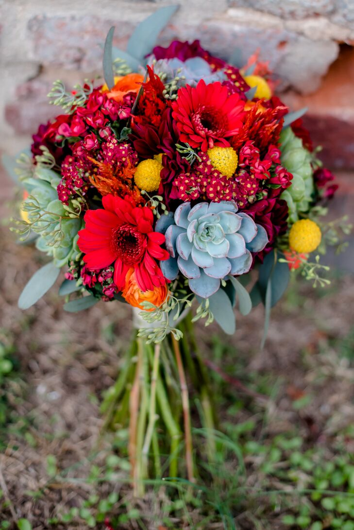"""Maggie carried a bouquet of yellow billy balls, orange ranunculus, burgundy dahlia, cottage red yarrow, mint green succulents, green seeded eucalyptus, red mini gerbera daisies, orange celosia and hot pink bouvardia. """"The bouquets were bright and semiautumnal but just looked colorful and happy,"""" she says."""